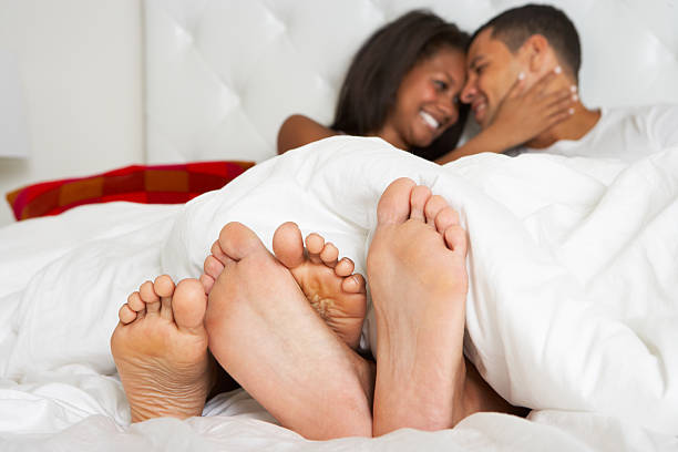 A couple relaxing in bed together stock photo