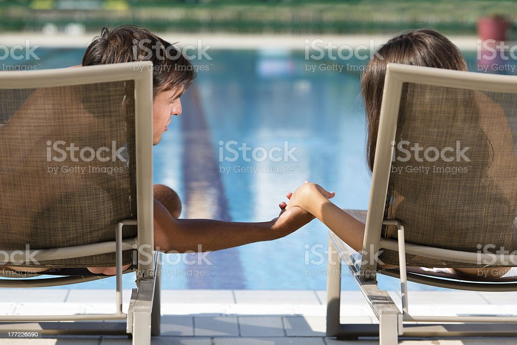 Couple relaxing in deck chairs by the swimming pool royalty-free stock photo
