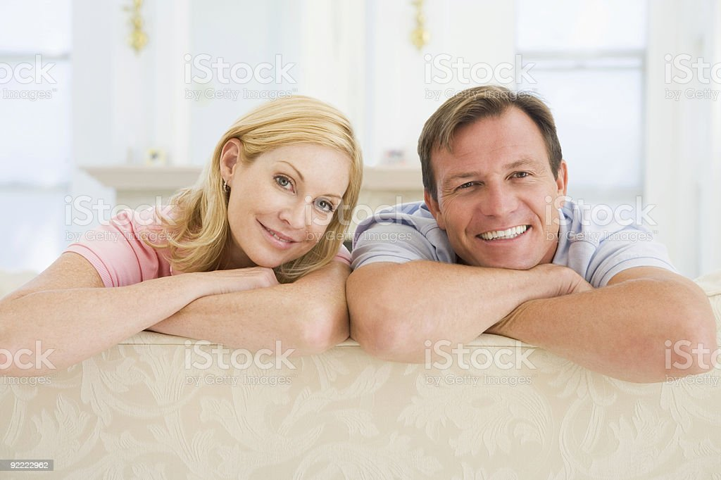 Couple relaxing in living room and smiling royalty-free stock photo