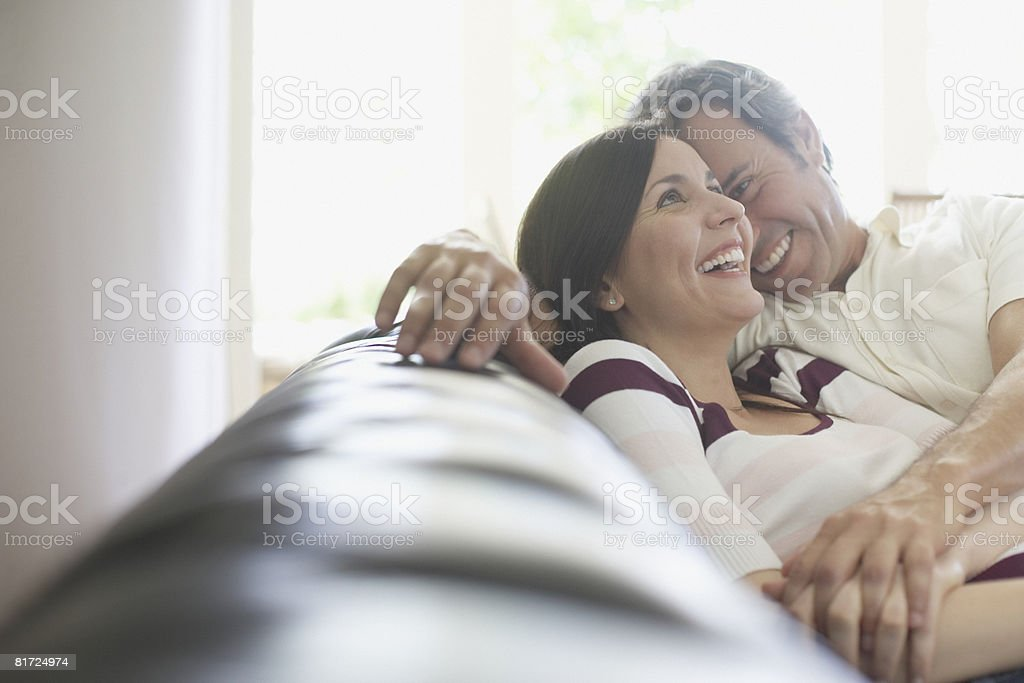 Couple relaxing in living room smiling stock photo