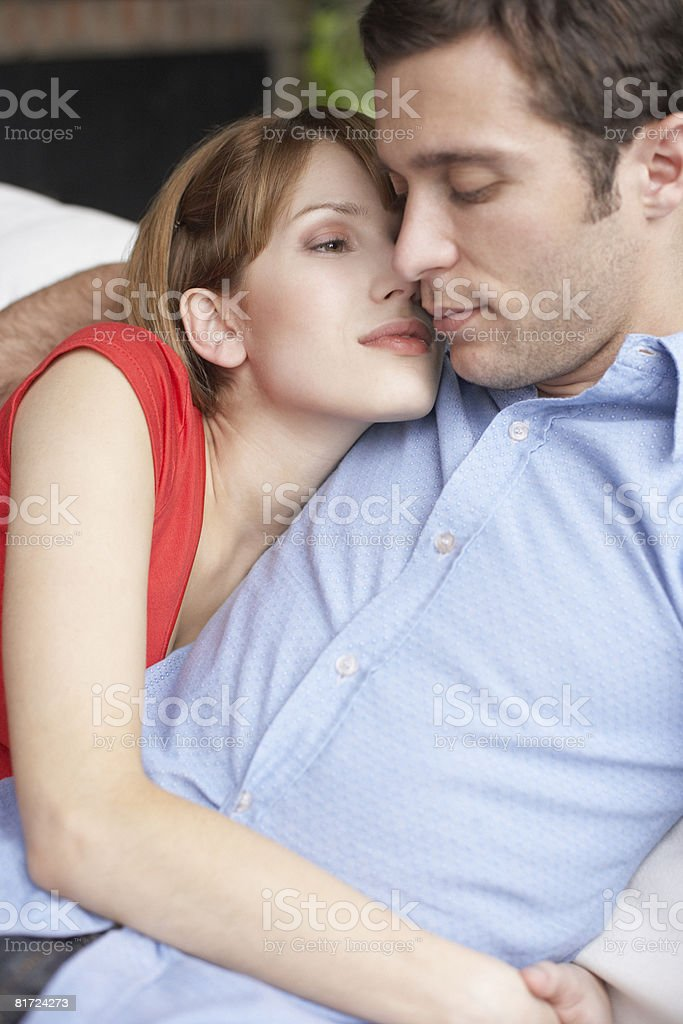 Couple relaxing in living room where the man is sleeping royalty-free stock photo