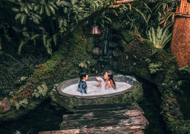couple relaxing in outdoor bath with tropical jungle  luxury spa hotel, lifestyle - mulher natureza flores e piscina imagens e fotografias de stock