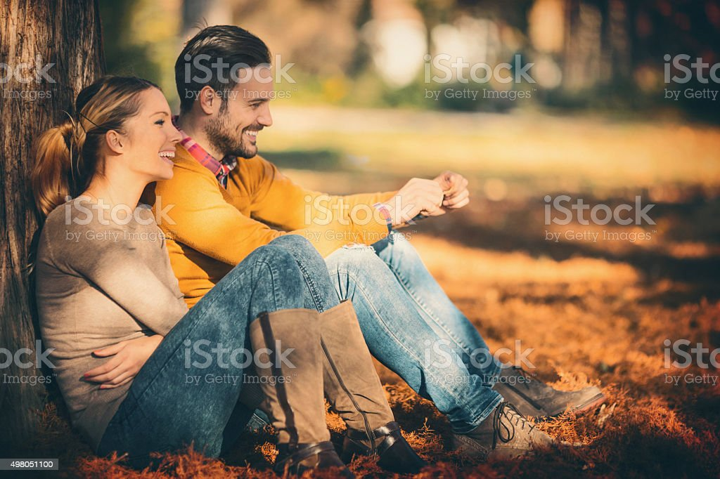 Closeup of late 20\'s happy couple enjoying warm October day in local...