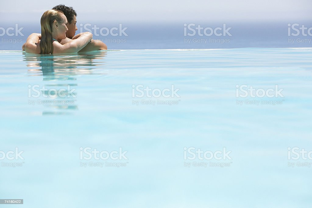 Couple relaxing in pool stock photo