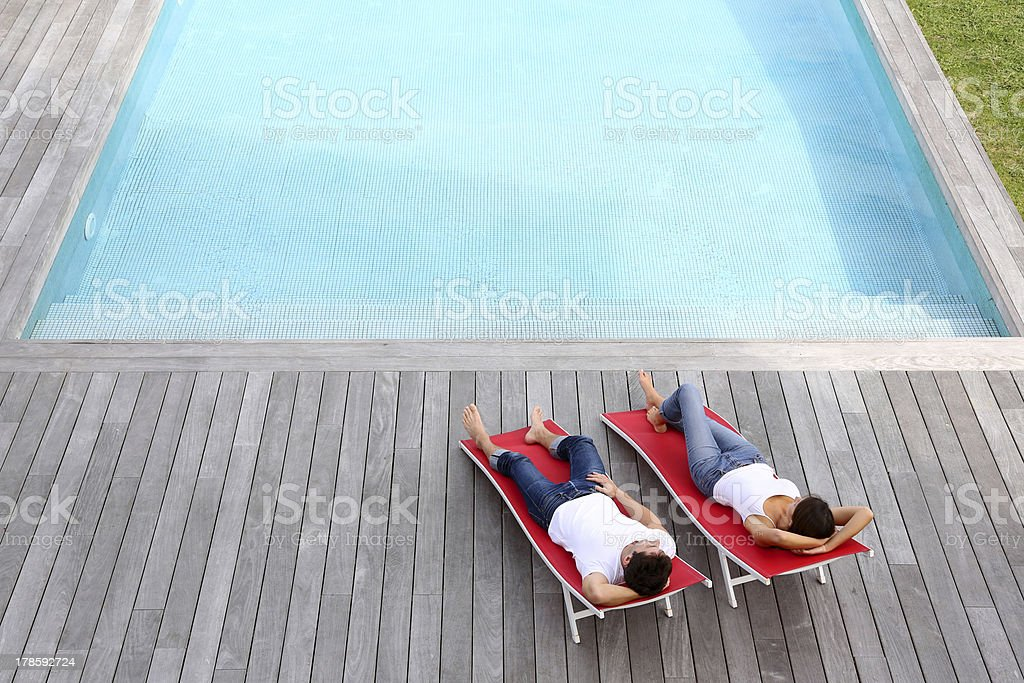Couple relaxing in red deck chairs by side pool stock photo