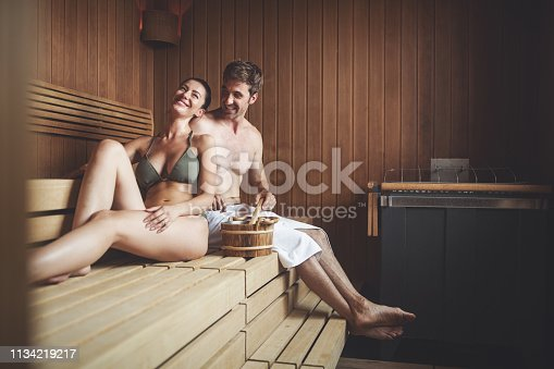 Beautiful couple relaxing in sauna and caring about health and skin