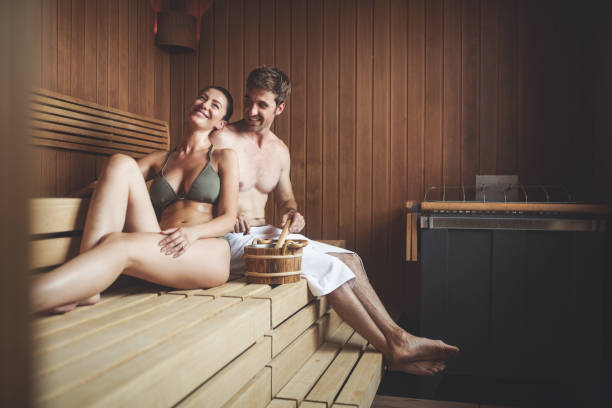 Couple relaxing in sauna and caring about health and skin Beautiful couple relaxing in sauna and caring about health and skin sauna stock pictures, royalty-free photos & images