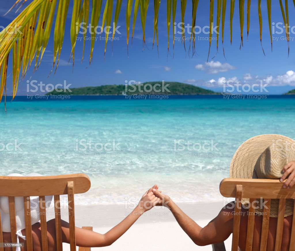 Couple relaxing in teak chairs on beautiful beach royalty-free stock photo