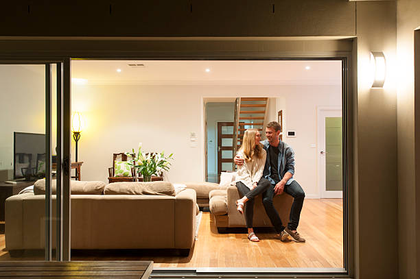 Couple relaxing in their home at night. Couple relaxing in their home at night. They are both wearing casual clothes and embracing. They are looking at each other and smiling. The house is contemporary with an open plan al fresco style. Copy space model home stock pictures, royalty-free photos & images