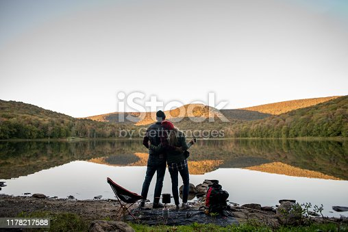 A couple that has hiked to a lake in the mountain side to camp and relax.