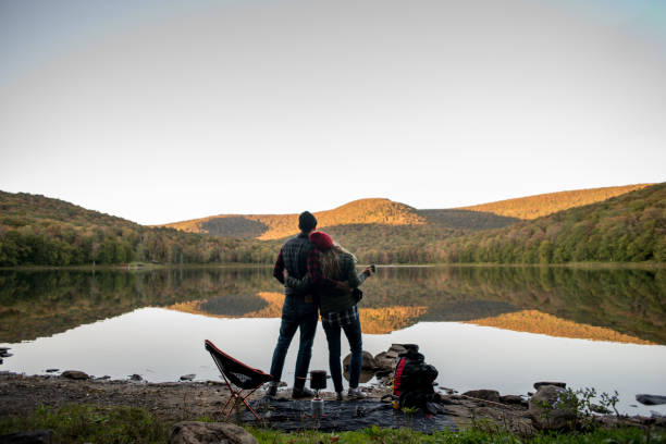 Couple relaxing near a lake while camping stock photo