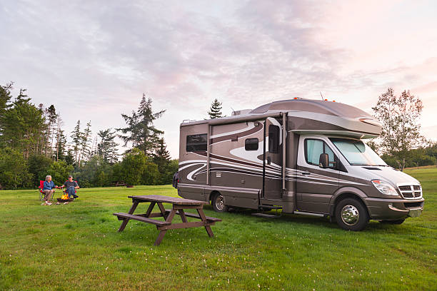 couple relaxing near campfire and motor home at dusk - motorhome stock photos and pictures