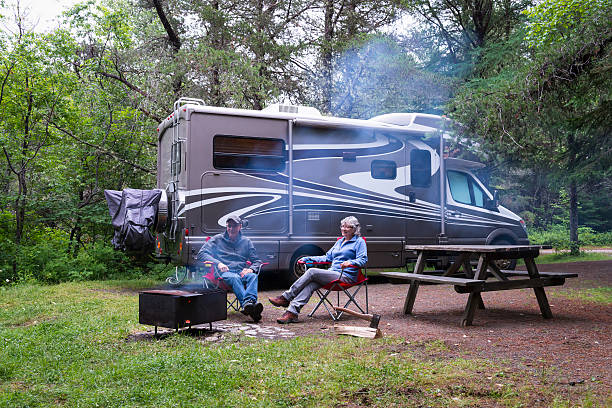 couple relaxing near campfire - motorhome stock photos and pictures