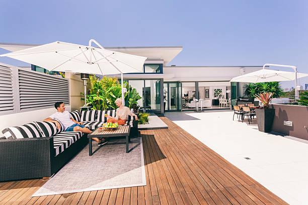 attraktives paar auf balkon - outdoor sonnenschutz stock-fotos und bilder
