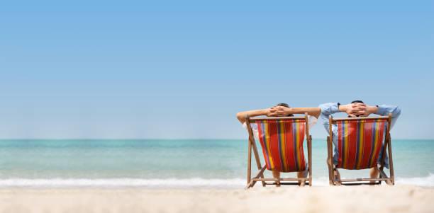 Pareja relajándose en la playa de la silla sobre el fondo del mar. - foto de stock