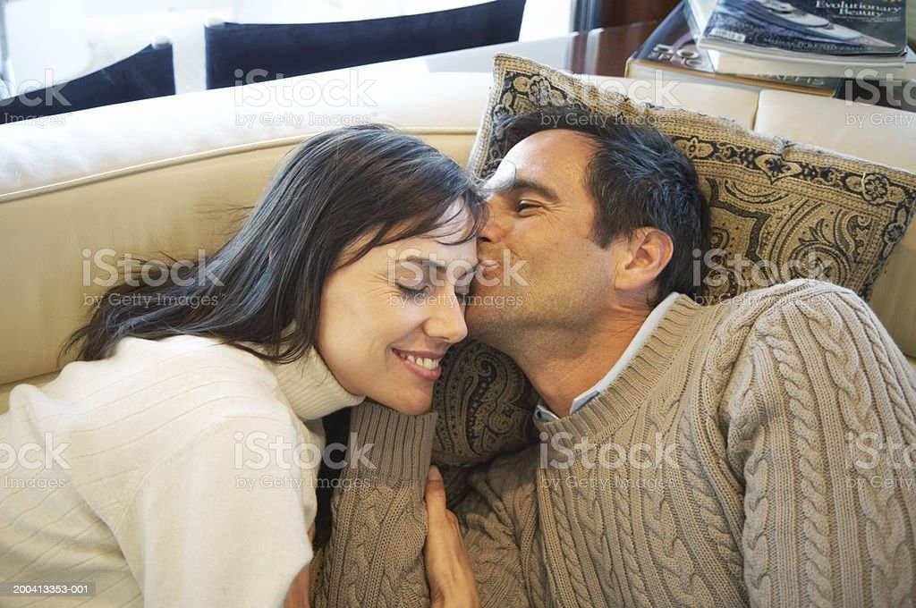 Couple relaxing on couch, man kissing woman's forehead stock photo