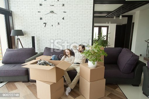 istock Couple relaxing on couch moving into new home with boxes 905222748