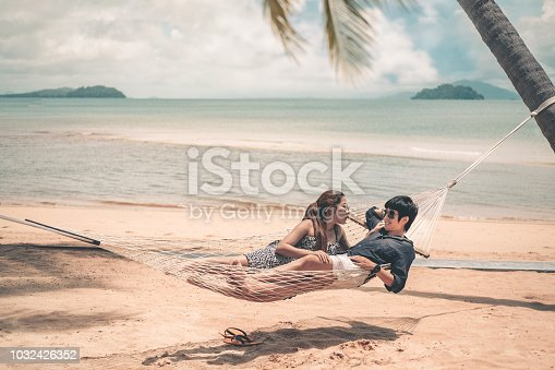 910783248 istock photo Couple relaxing on hammock summer holiday on beach 1032426352