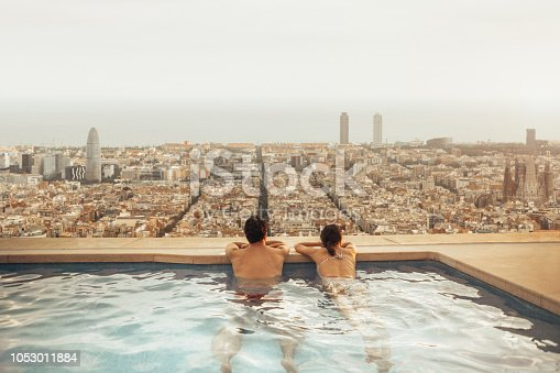 istock Couple relaxing on hotel rooftop looking at Barcelona city skyline. Photo composition. 1053011884