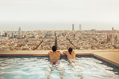Couple relaxing on hotel rooftop looking at Barcelona city skyline. Photo composition.