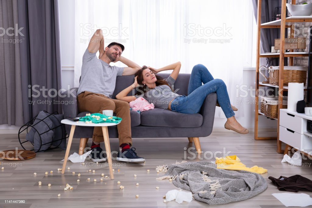 Smiling Couple Relaxing On Sofa In Messy Living Room At Home