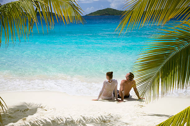couple relaxing on the beach - caribbean stock pictures, royalty-free photos & images
