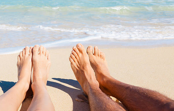 couple relaxing on the beach - woman leg beach pov stock photos and pictures