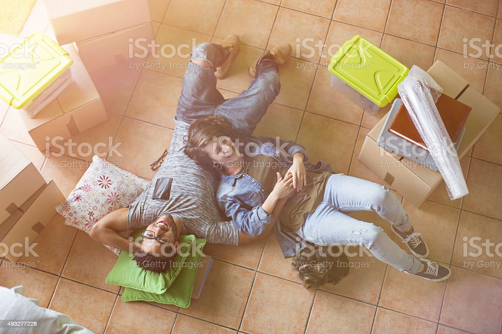 Couple relaxing on the floor at their new home stock photo
