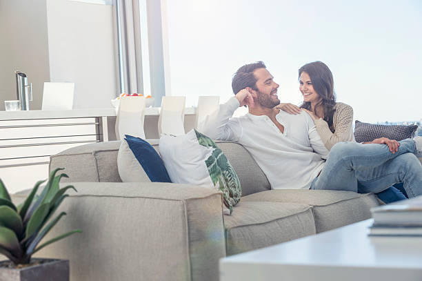 couple relaxing on the sofa. - modern lifestyle stock photos and pictures