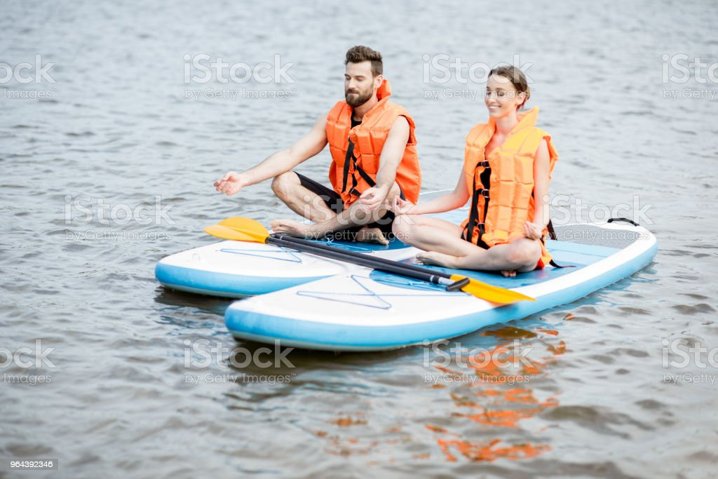 Casal relaxando sobre o stand up paddleboard - Foto de stock de Adulto royalty-free