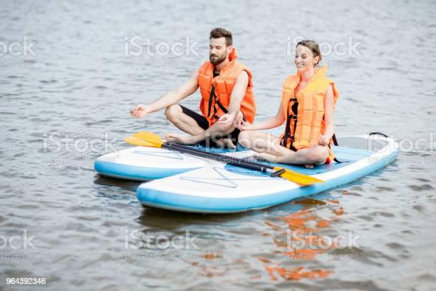 Foto de Casal Relaxando Sobre O Stand Up Paddleboard e mais fotos de stock de Adulto