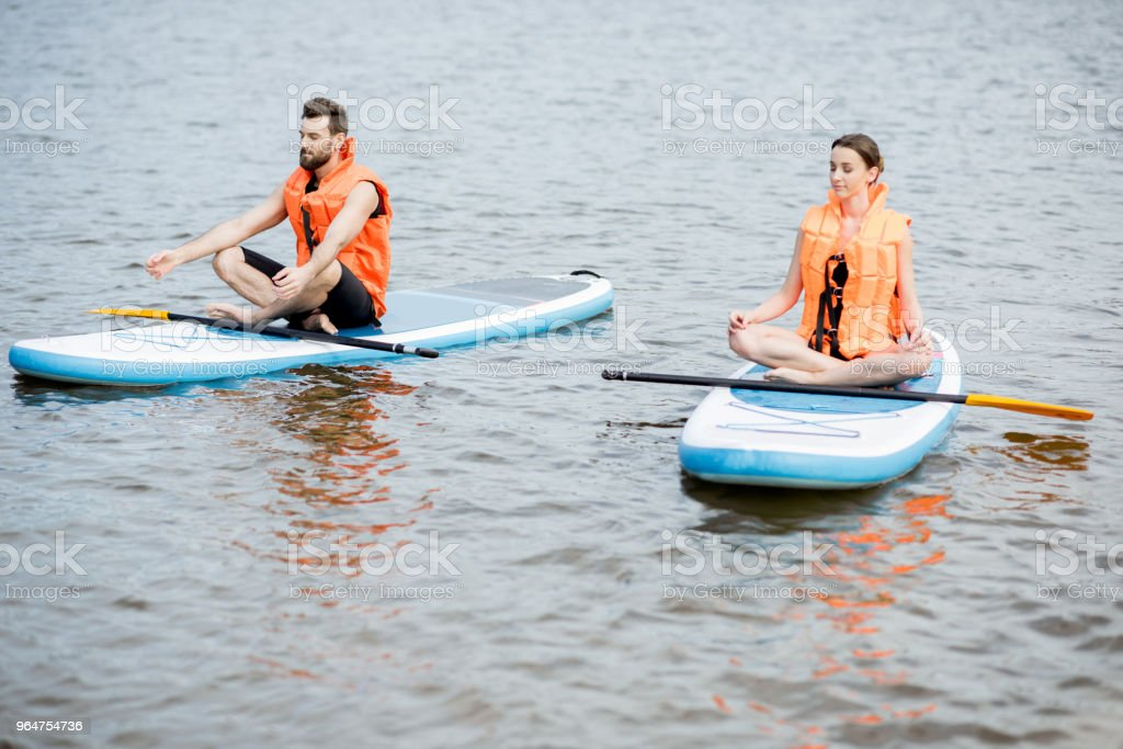 Couple relaxing on the stand up paddleboard royalty-free stock photo