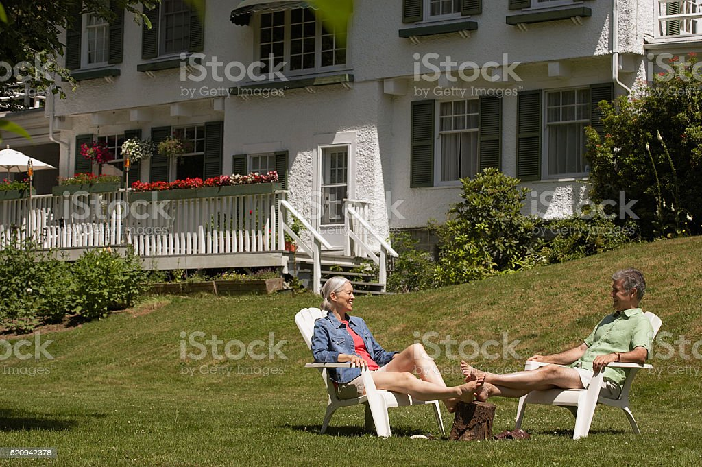Couple relaxing on their lawn stock photo