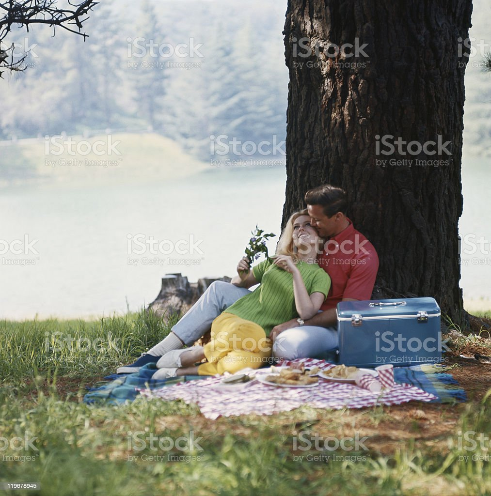 Couple relaxing under tree stock photo