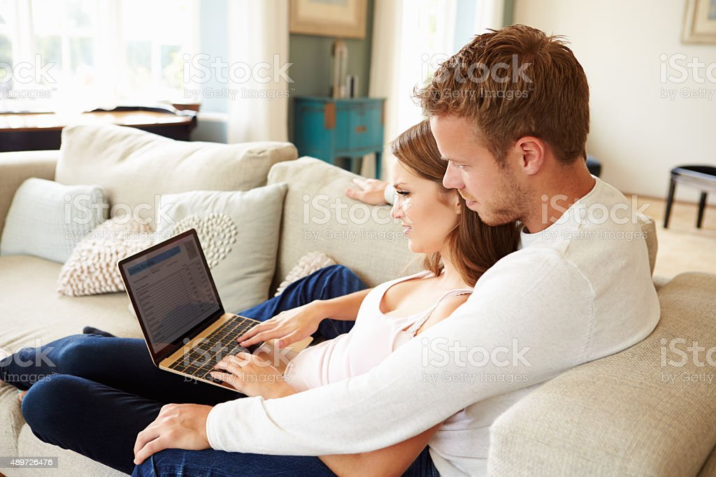 Couple Relaxing Using Laptop Computer For Internet Banking stock photo