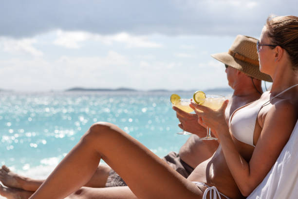 Couple relaxing with cocktail in a teak lounge chairs on a tropical beach