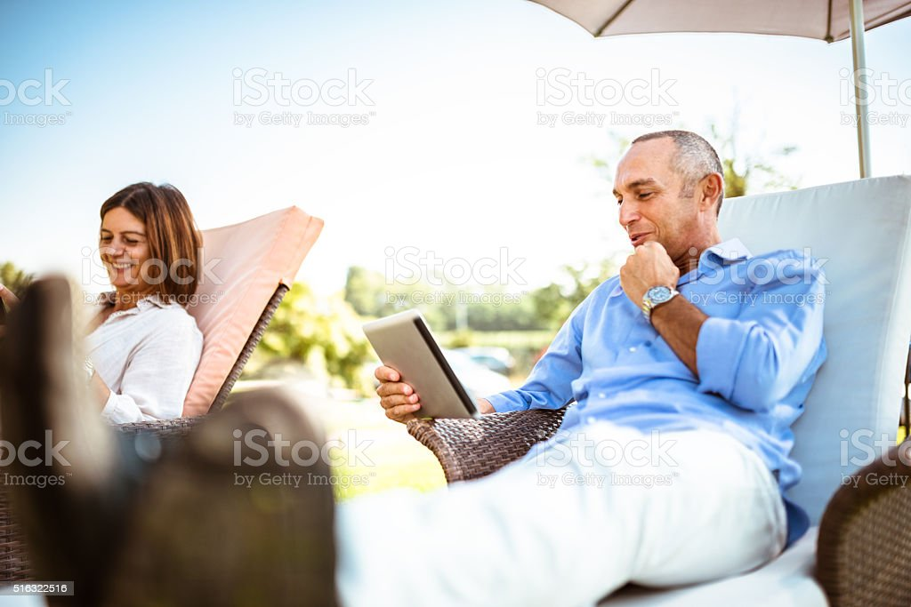 couple relaxing with multimedia device at the resort stock photo