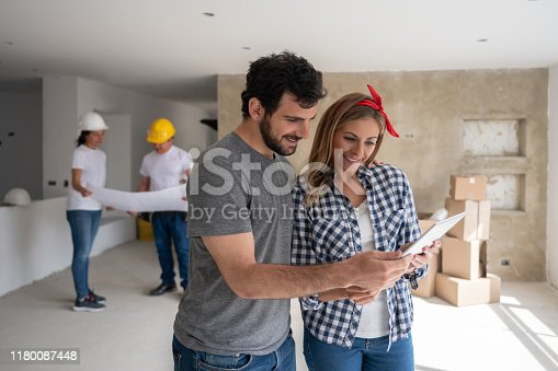 istock Couple remodeling their house and looking at the design on a tablet computer 1180087448
