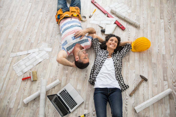 Couple renovating and resting on floor Couple renovating their home, resting and lying down on floor, high angle view. home addition stock pictures, royalty-free photos & images