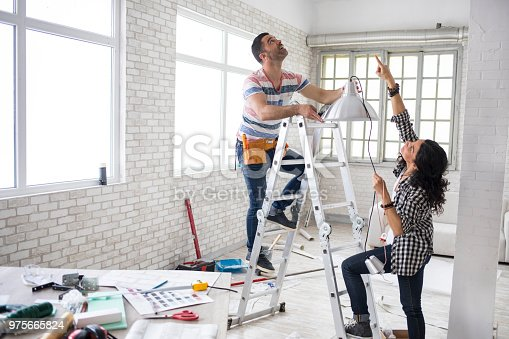 Young woman and a construction worker renovating an apartment.