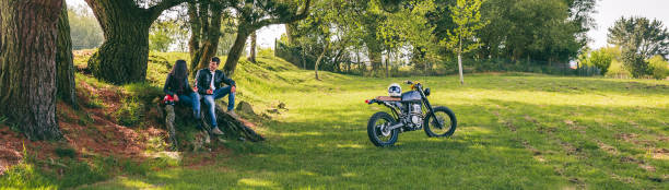 Couple resting from a motorcycle trip Young couple resting from a motorcycle trip having a beer outdoors female biker resting stock pictures, royalty-free photos & images