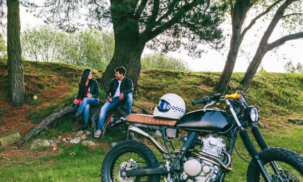 Couple resting from a motorcycle trip Young couple resting from a motorcycle trip having a beer outdoors with motorbike in foreground. Selective focus on couple in the background female biker resting stock pictures, royalty-free photos & images