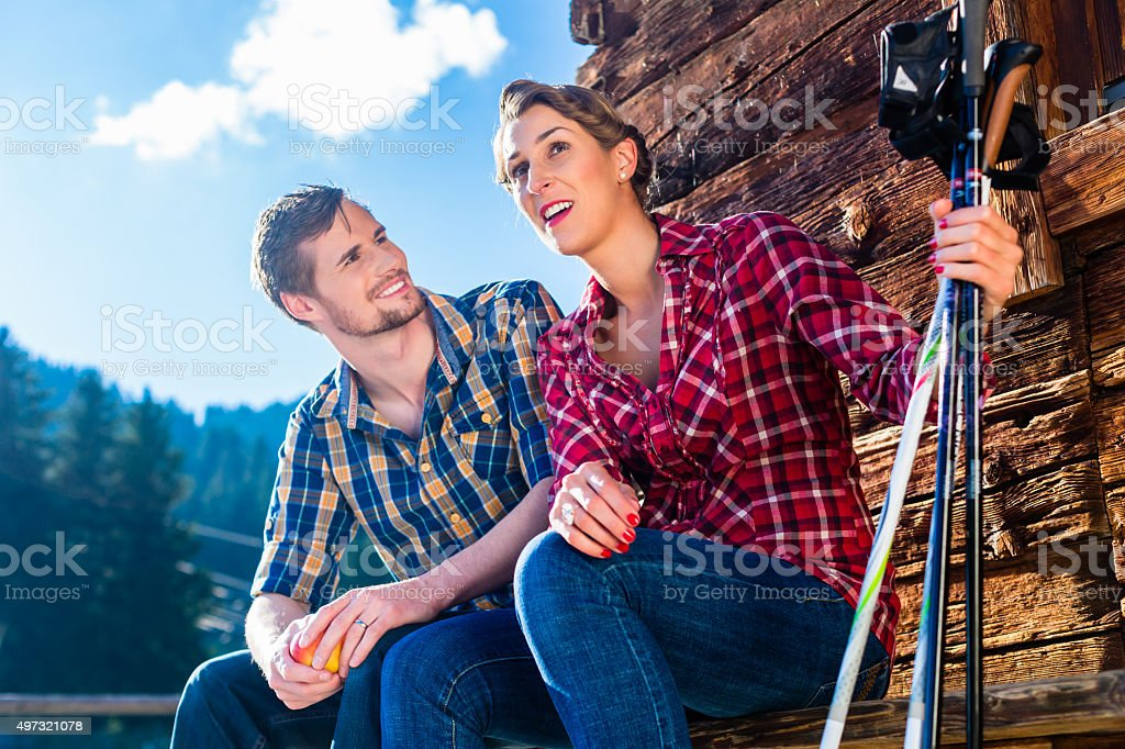 Couple resting from nordic walking in mountain cabin stock photo