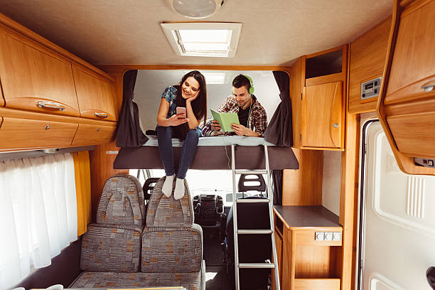 Couple resting in campervan Young couple on a vacation rv interior stock pictures, royalty-free photos & images