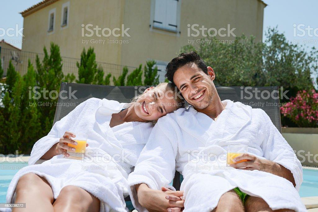 カップルで休息のデッキチェアとプールサイドでのバスローブ ストックフォト