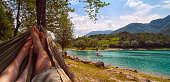 Couple resting in hammock (view from hammock) on sunny beach of mountain lake, blue sky with white clouds, Lago di Tenno, Italy