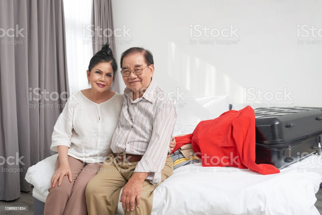 Happy senior Vietnamese couple sitting in hotel room with clothes and...