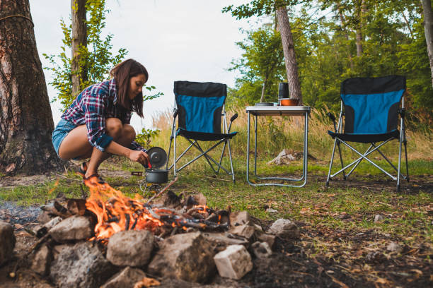 couple resting near bonfire. woman cooking outdoors on fire. hiking concept stock photo
