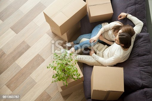 938682826istockphoto Couple resting on couch moved into new home, top view 951363782