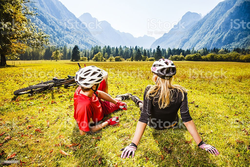 Couple resting on grass after mountain biking royalty-free stock photo